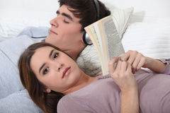 A teenage couple. Resting on their bed Royalty Free Stock Images