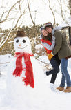 Teenage Couple Building Snowman Royalty Free Stock Image