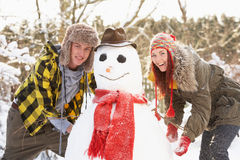 Teenage Couple Building Snowman Stock Photography