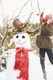 Teenage Couple Building Snowman Stock Images
