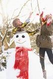Teenage Couple Building Snowman Stock Images