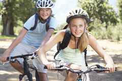 Teenage Couple Cycling Through Countryside Stock Photography