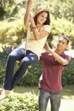 Teenage Couple Having Fun On Rope Swing royalty free stock photos