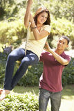 Teenage Couple Having Fun On Rope Swing Stock Image