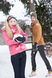 Teenage Couple Having Snowball Fight. In Snowy Landscape royalty free stock images