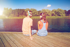 Teenage couple with headphones on river berth Stock Images