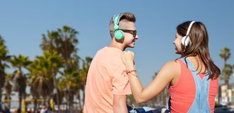 Teenage couple with headphones at venice beach. Summer holidays, vacation, love and technology concept - happy teenage couple with headphones sitting on river Stock Image