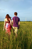 Teenage couple holding hands. A back view of a teen couple holding hands walking in a field Royalty Free Stock Image