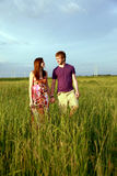 Teenage couple holding hands. A front view of a teen couple holding hands walking in a field Stock Image