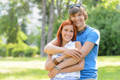 Teenage couple hugging in sunny park smiling Stock Photography