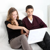 Teenage couple laughing at their laptop Stock Photography