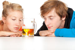 Teenage couple leaning on table with beer Stock Images