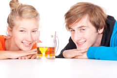 Teenage couple leaning on table with beer Royalty Free Stock Photography