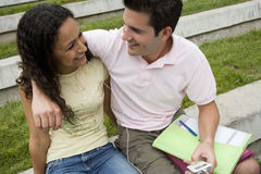 Teenage couple (17-19) listening to MP3 player, sharing headphones, boy with arm around girl Royalty Free Stock Images