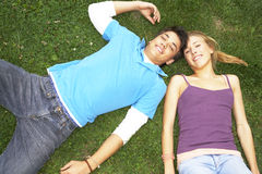 A teenage couple lying down on the grass. Royalty Free Stock Images