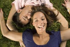 A teenage couple lying down on the grass. Royalty Free Stock Photo