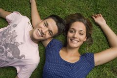 A teenage couple lying down on the grass. Stock Photos