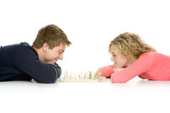 Teenage couple lying down playing chess Stock Image