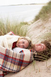 Teenage Couple Lying In Sand Dunes. Wrapped In Blanket Stock Image