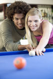 A teenage couple playing pool Royalty Free Stock Images