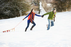 Teenage Couple Pulling Sledge Across Snowy Field Stock Photography
