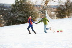 Teenage Couple Pulling Sledge Across Snowy Field Royalty Free Stock Image