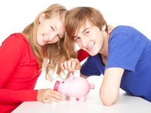 Teenage couple putting money to piggy bank Royalty Free Stock Photos
