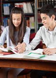 Teenage Couple Reading Book Together In Library. Teenage couple reading book together while holding hands at desk in library Stock Photos