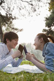 Teenage couple reading books in the park Stock Images