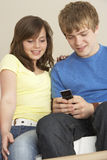 Teenage Couple Reading Text Message Stock Image