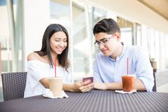 Couple Reading Message On Smartphone In Cafe At Shopping Mall royalty free stock photos