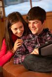 Teenage Couple Relaxing On Sofa With Laptop Stock Photography
