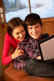 Teenage Couple Relaxing With Tablet Computer. Teenage Couple Relaxing On Sofa With Tablet Computer In Chalet On Ski Holiday Stock Photography