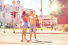 Teenage couple riding skateboards on city street Stock Photography