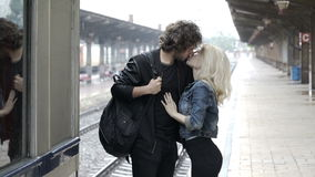 Teenage couple saying goodbye on train station platform stock footage