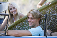 Teenage couple (17-19) sitting in car with surfboard, smiling, side view, portrait Royalty Free Stock Photo