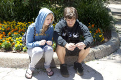 Teenage Couple Sitting on Curb. Two teenagers, a boy and a girl, white, sitting on a curb with flowers behind them.  They look pensive, as if something is Stock Photos