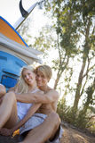Teenage couple (17-19) sitting on ground beside car and surfboard, smiling, portrait (tilt) Stock Photography