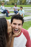 Teenage couple (17-19) sitting near friends, girl kissing boy on cheek, smiling Stock Photo
