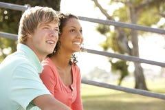 Teenage Couple Sitting In Playground. Smiling Teenage Couple Sitting In Playground Stock Images