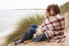 Teenage Couple Sitting In Sand Dunes. Wrapped In Blanket Royalty Free Stock Photography