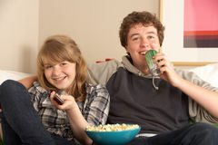 Teenage Couple Sitting On Sofa Watching TV. With popcorn Stock Images