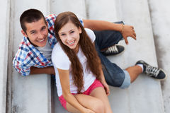 Teenage couple sitting on stairs. Portrait of young couple outdoors Stock Photo