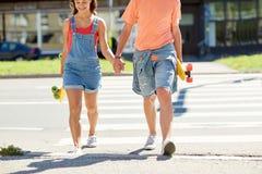Teenage couple with skateboards at city crosswalk Stock Photos