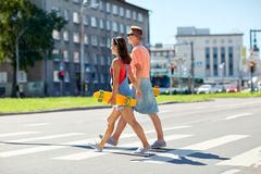 Teenage couple with skateboards on city crosswalk Royalty Free Stock Images