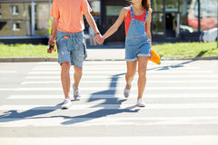 Teenage couple with skateboards on city crosswalk Royalty Free Stock Photography