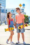 Teenage couple with skateboards on city street Royalty Free Stock Images