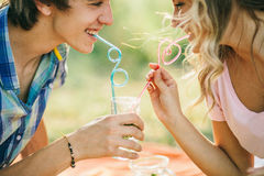 Teenage couple smiling with cocktail. Teenage couple drink cocktail from one glass and smiling royalty free stock image