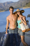 Teenage couple (17-19) standing near lake, boy holding inflatable, girl wearing sun hat, portrait Royalty Free Stock Photo