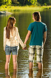 Teenage couple standing in water holding hands Royalty Free Stock Photo